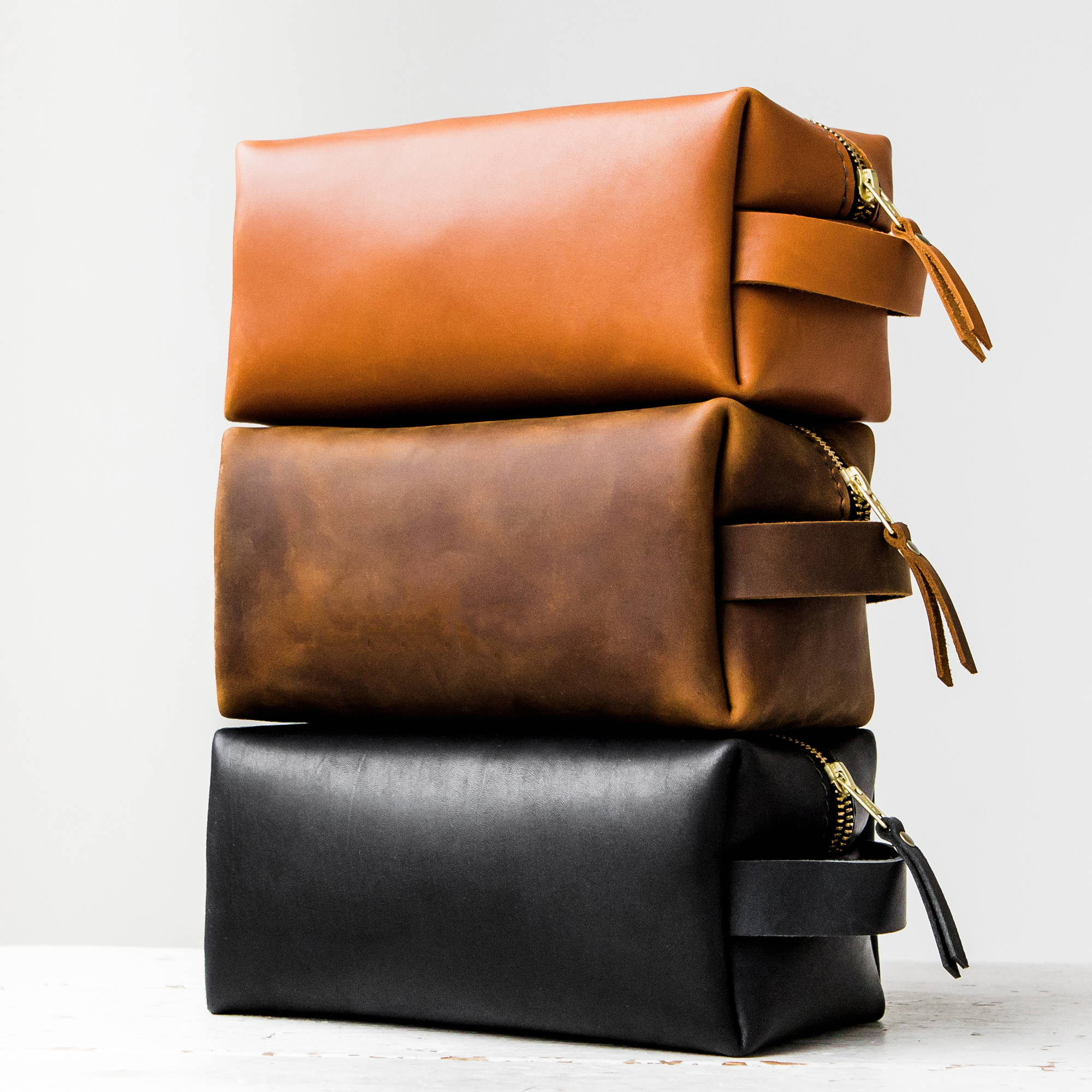 stack of three colors of handmade leather dopp kit