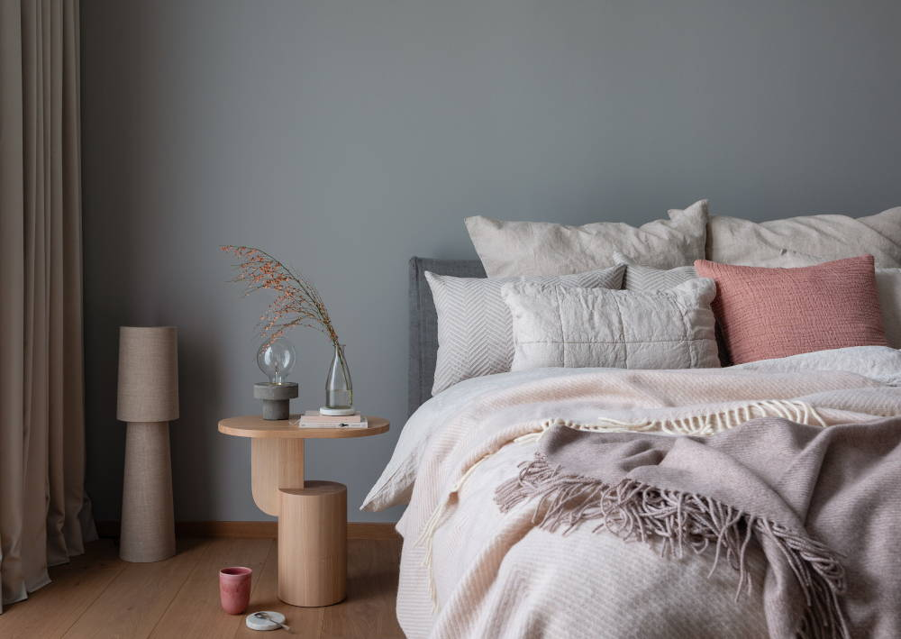 Bedroom with pink and beige pillows, bedspread and soft blanket; side table with concrete lamp