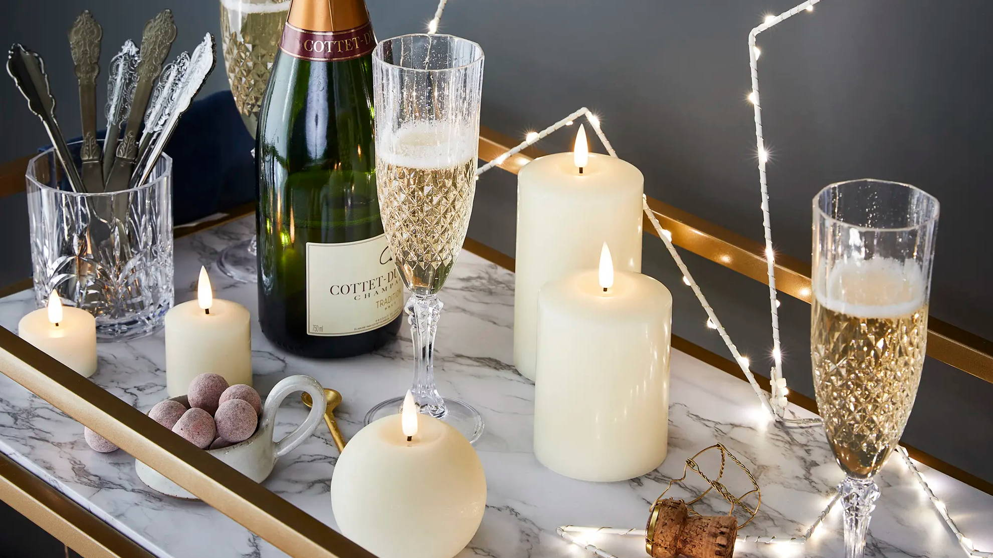 Star light and TruGlow candles styled as part of New Year's table with champagne glasses