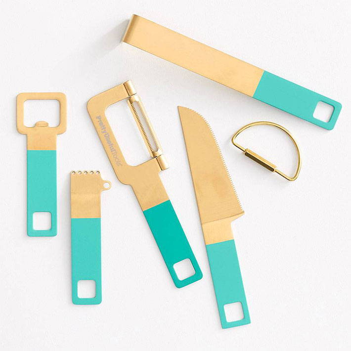 A set of cocktail tools that are gold tipped and turquoise handles.