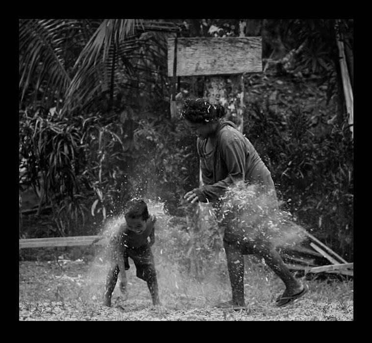 a mother and her child splashing each other with water