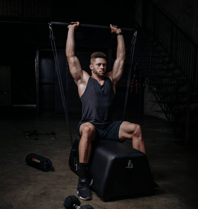 model demonstrates a military/overhead press with workout bench, resistance bands, and bar attachment.