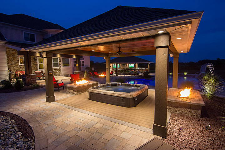 Stunning patio overhang with  dual fire pits and relaxing jacuzzi in the middle.