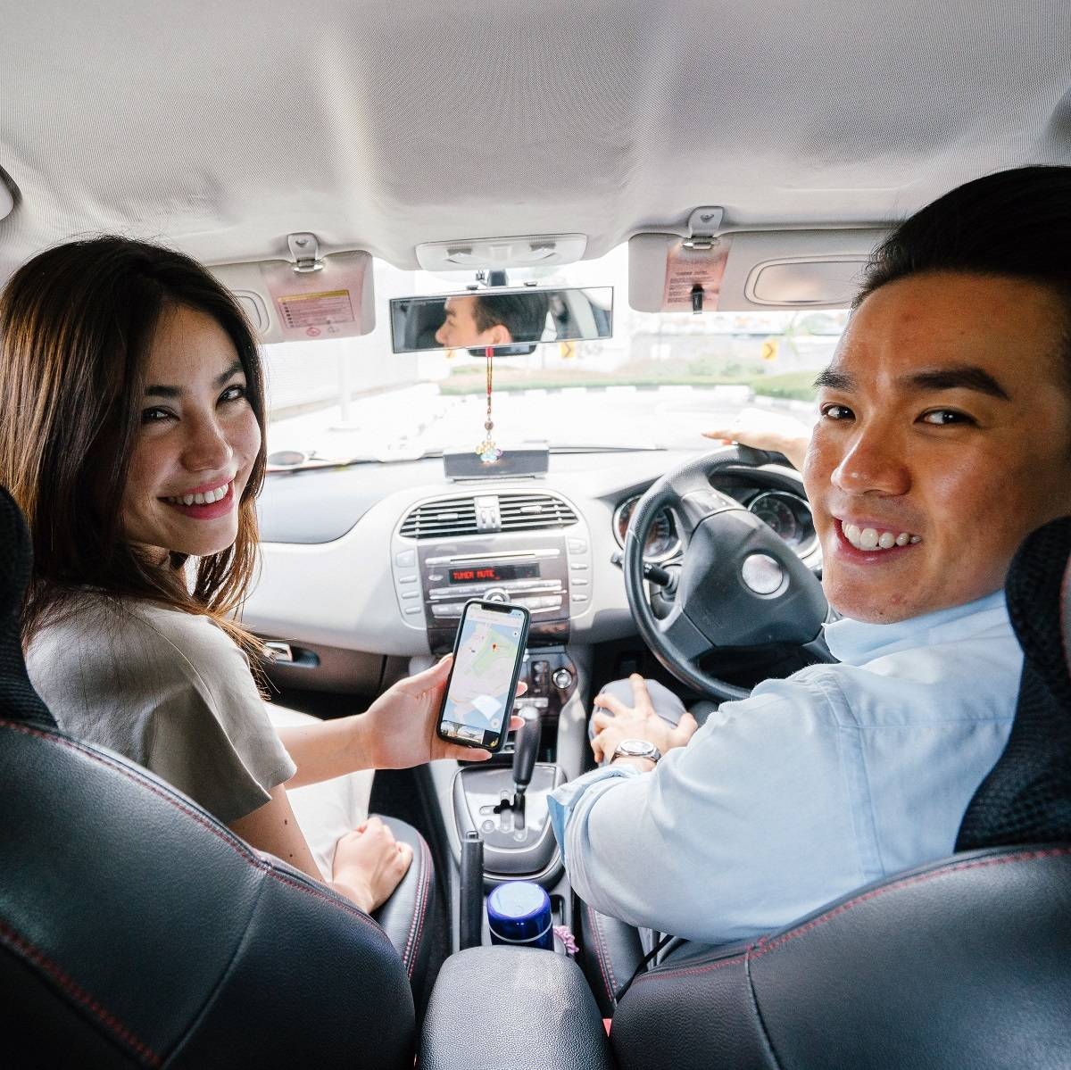 A lady and a man sharing a ride as part of a carpooling scheme