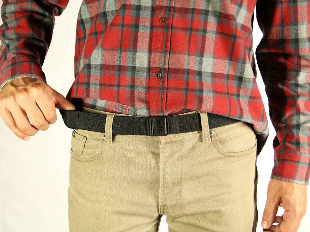 Man wearing a JeltX Adjustable stretch belt in black. Pictured stretching the belt from khaki pants.