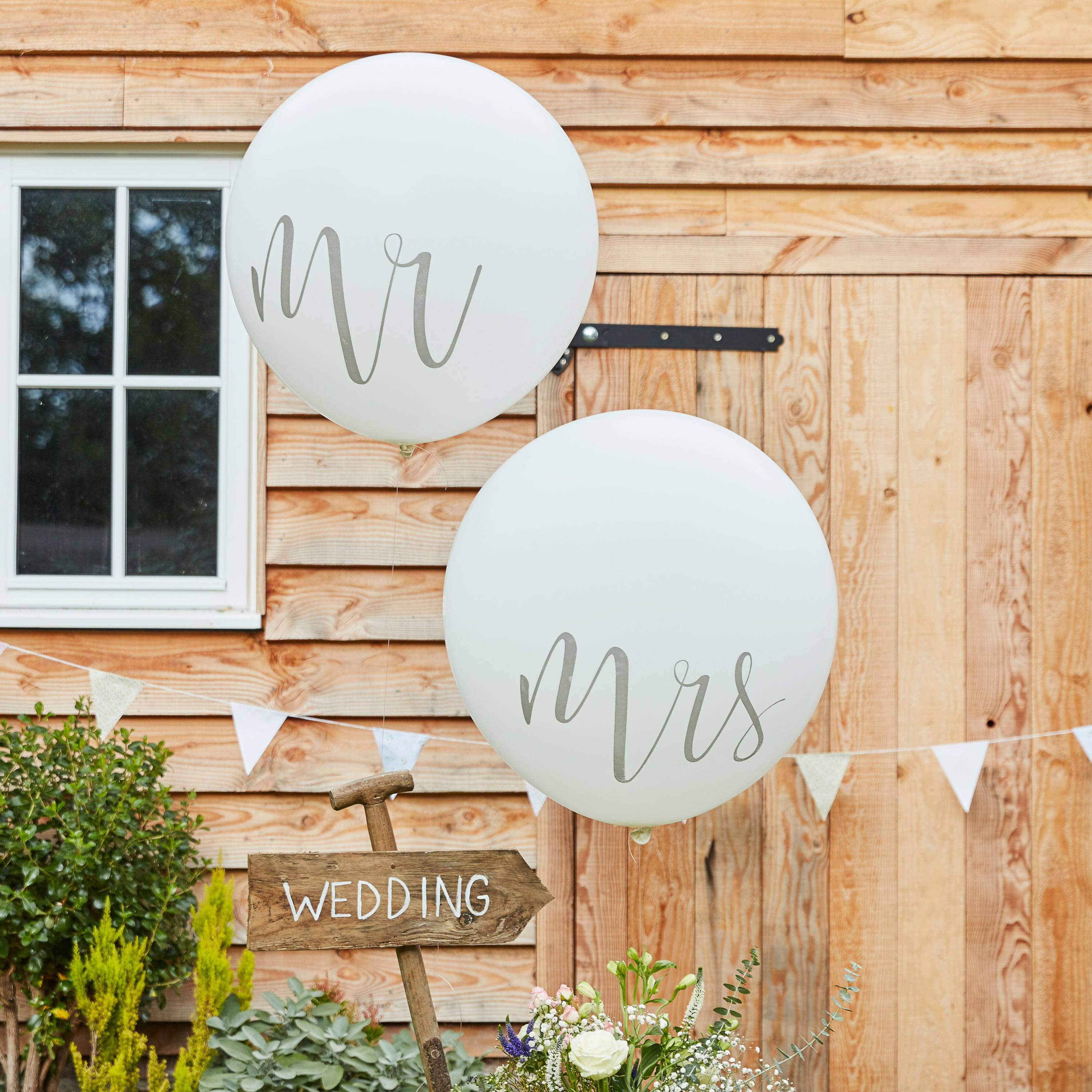 A photo of two white wedding balloons, one saying 'Mr' and one saying 'Mrs' blown up against a rustic barn wedding with white bunting and a wooden sign pointing to the wedding.