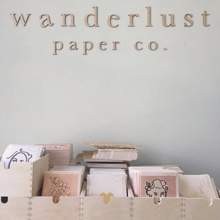 Wanderlust cards stacked up underneath a Wanderlust wall sign.