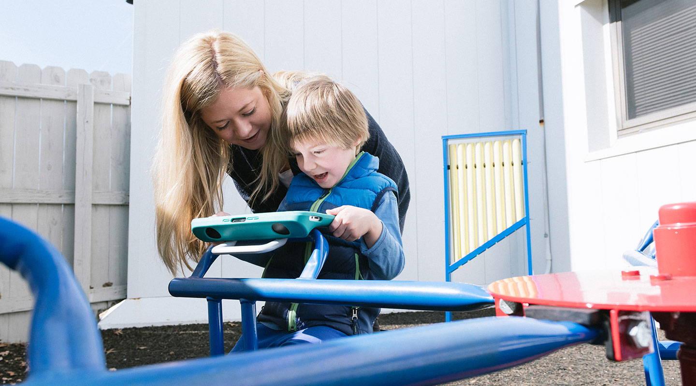 Mutter kommuniziert mit ihrem Sohn auf dem Spielplatz mit einem Tobii Dynavox UK-Gerät.