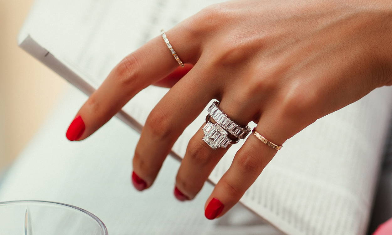 Model wearing Ring Concierge bespoke engagement ring and eternity band holding a newspaper