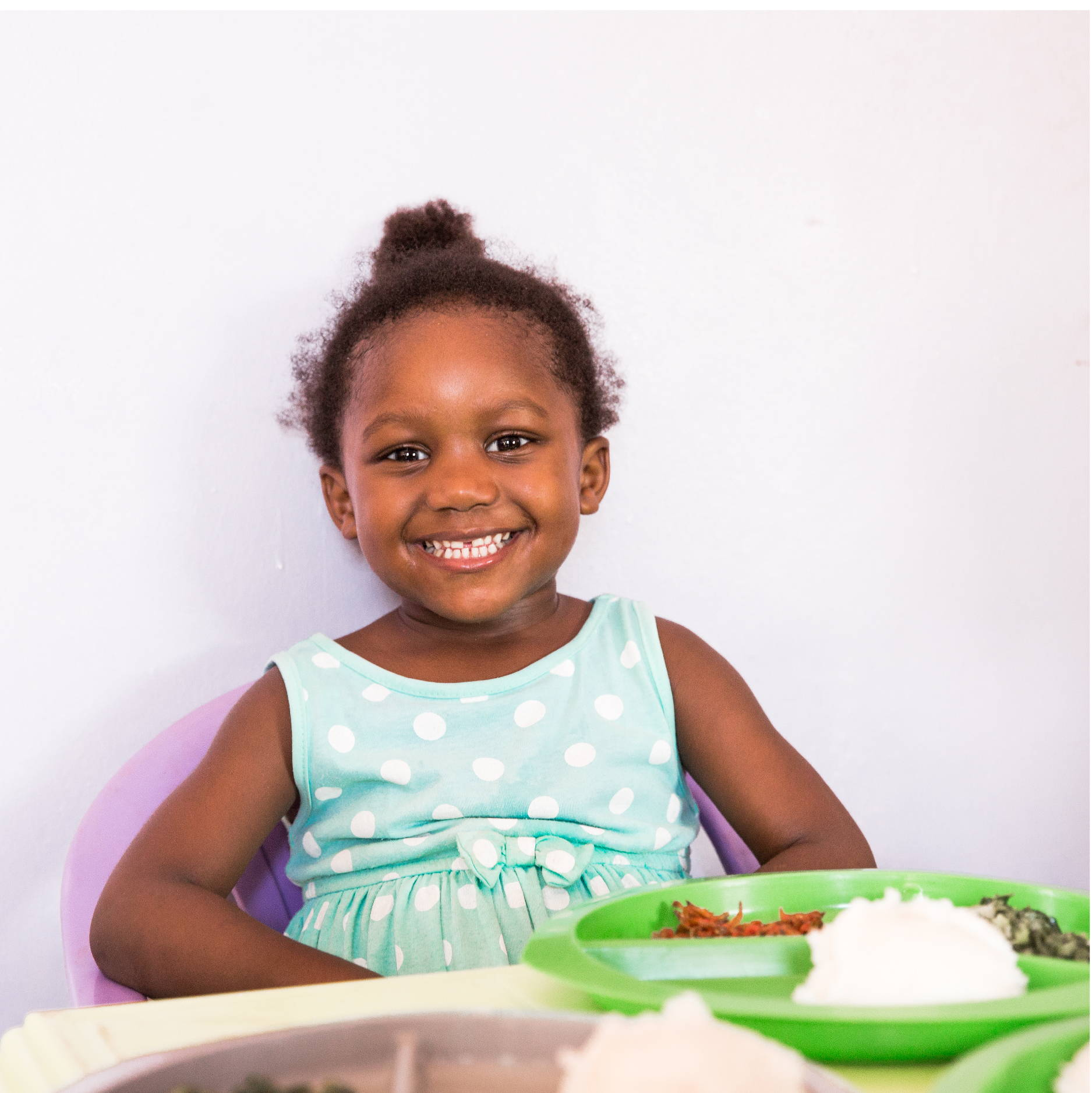A small Zambian girl in a blue polka dotted dress gives a big smile, showing her teeth, as she sits to eat lunch.