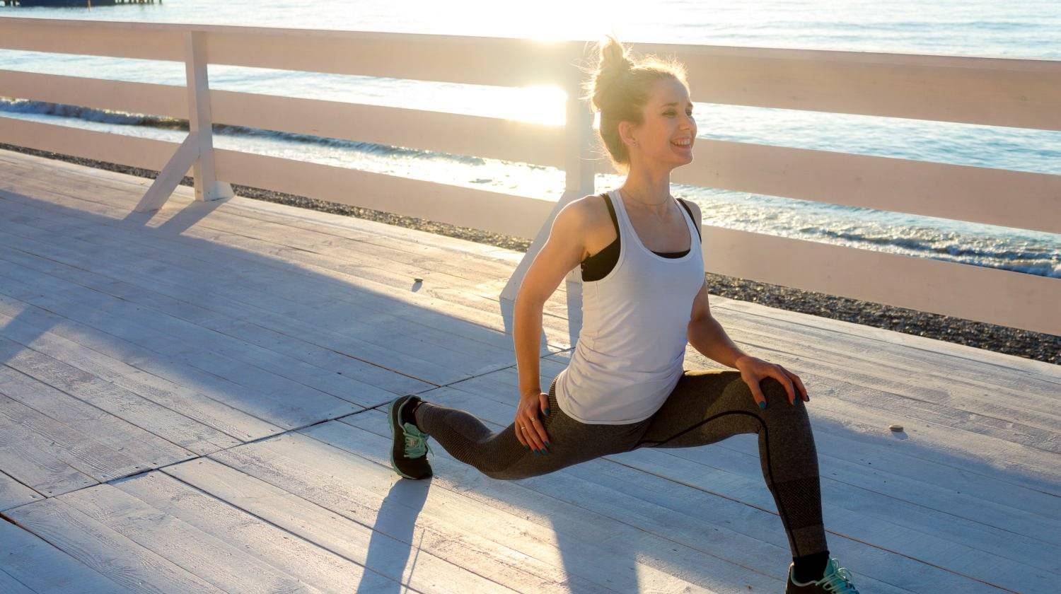 Slim woman stretching legs in deep lunge   Reasons To Start Your Day With A Morning Workout   morning exercise routine   Featured