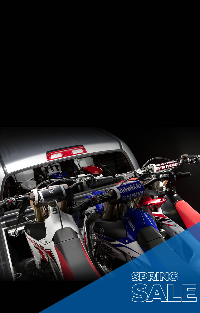 Three dirt bike motorcycles in the cargo bed of a pickup truck.