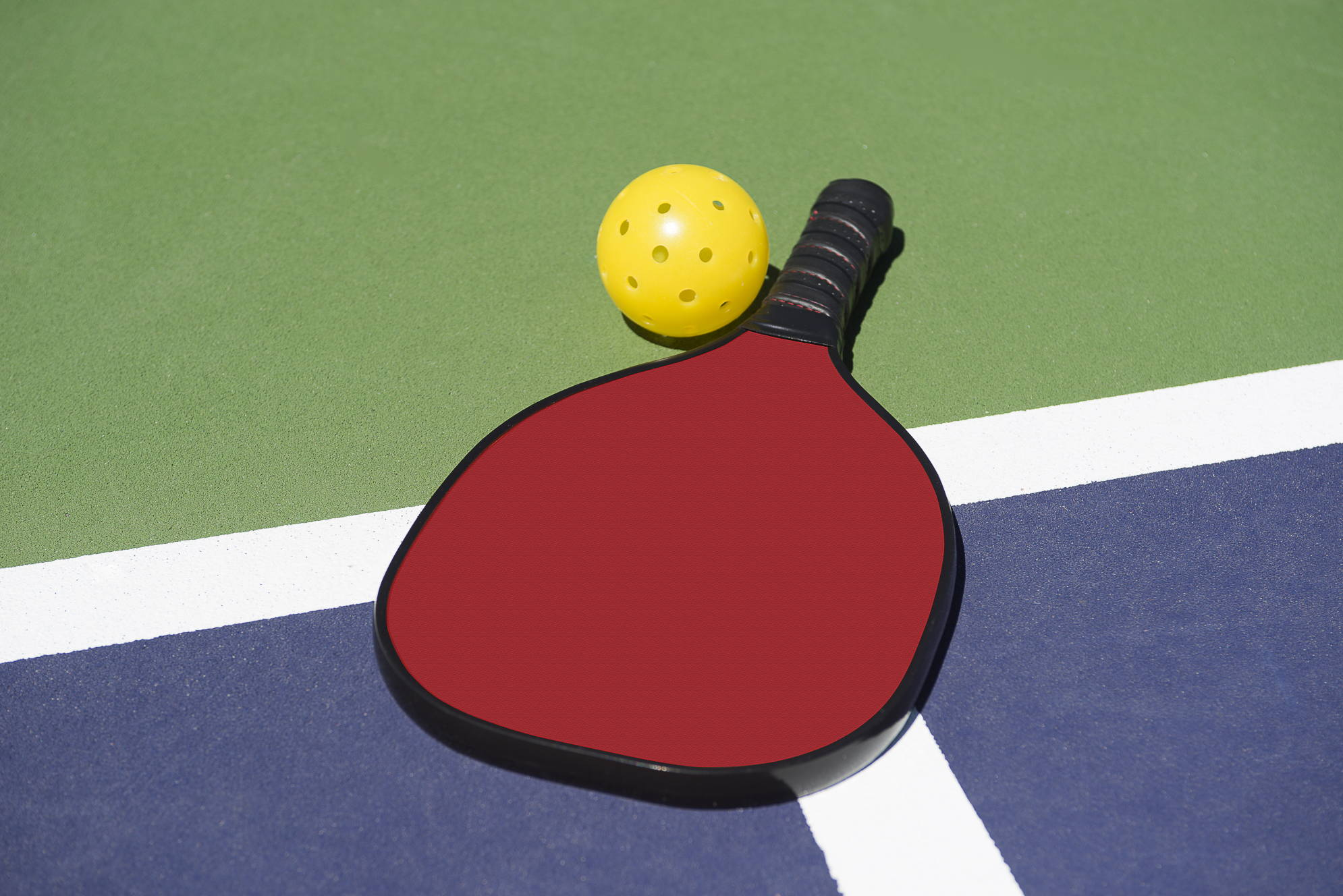 pickleball and pickleball paddle on court