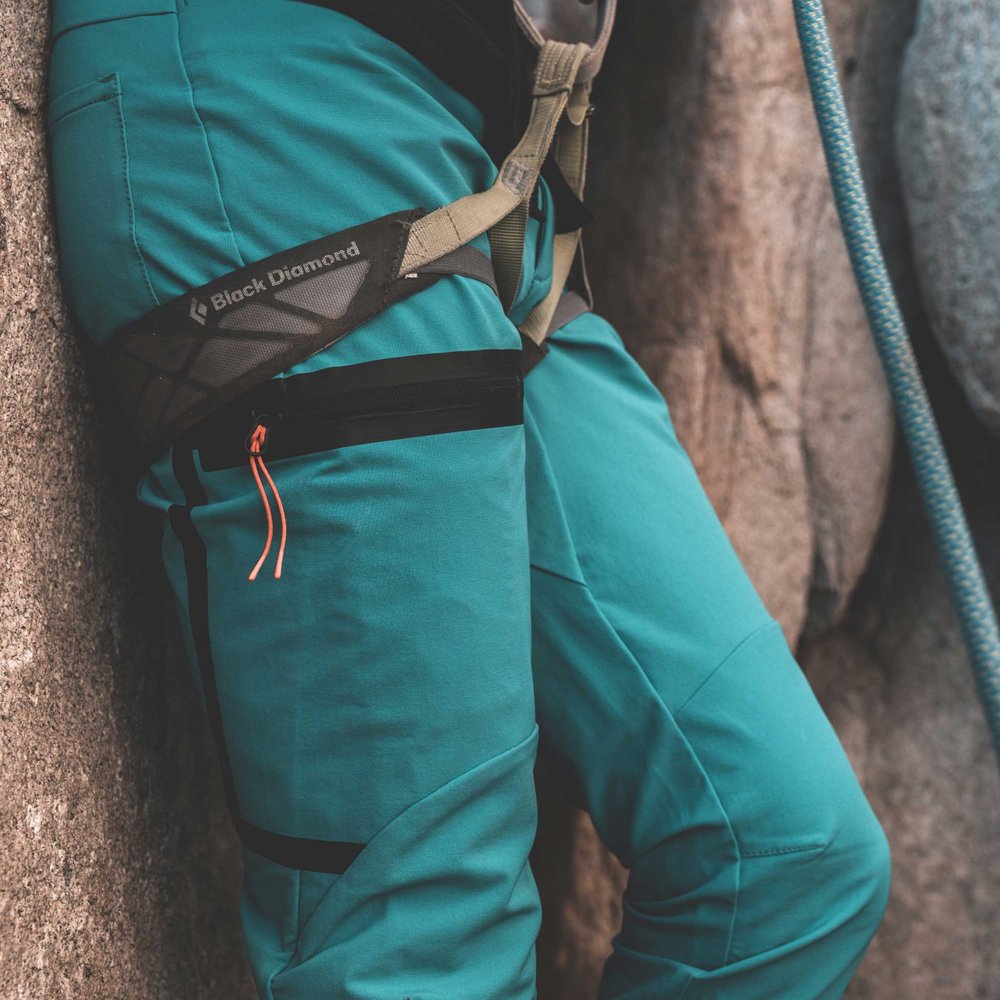 Man belaying rock climber wearing Foehn Brise Pant