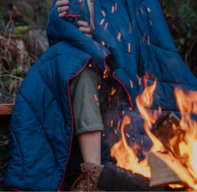 A man sitting around the campfire wrapped in a Rumpl blanket