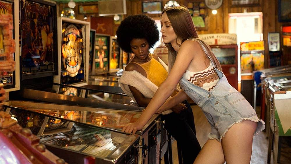 Two women in 70s style clothing in an arcade
