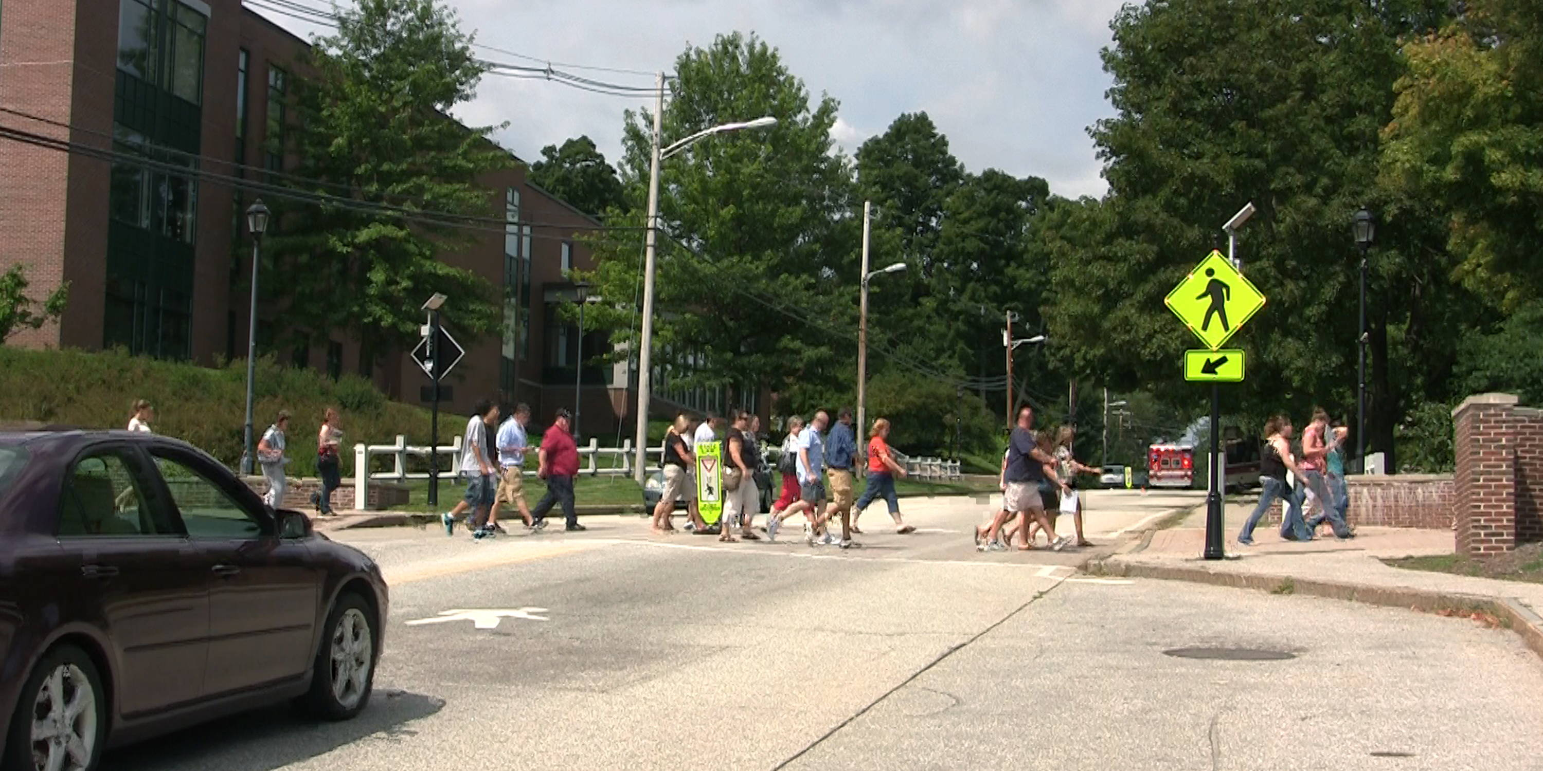 Busy intersection with several people crossing the street near a blinkersign.
