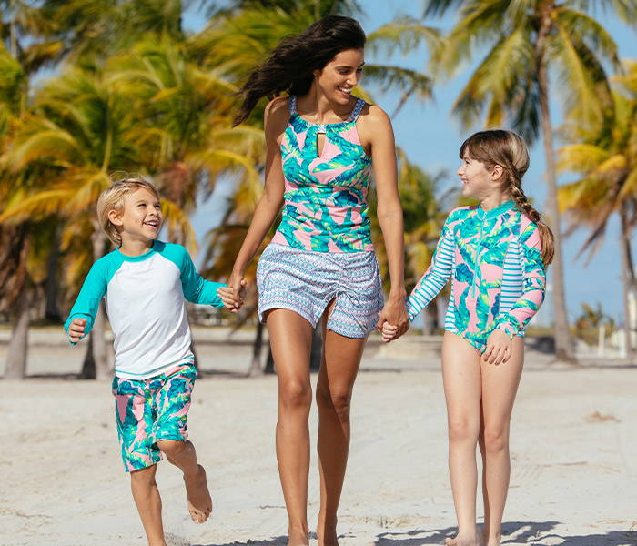 Boy wearing Preppy Palm Swim Shorts And Rashguard Set, mom wearing Preppy Palm Tankini and Preppy Palm Side Tie Swim Skirt & girl wearing Preppy Palm Unisuit