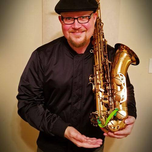 Roots saxophonist Ian Hendrickson-Smith holding tenor saxophone with Key Leaves sax key props