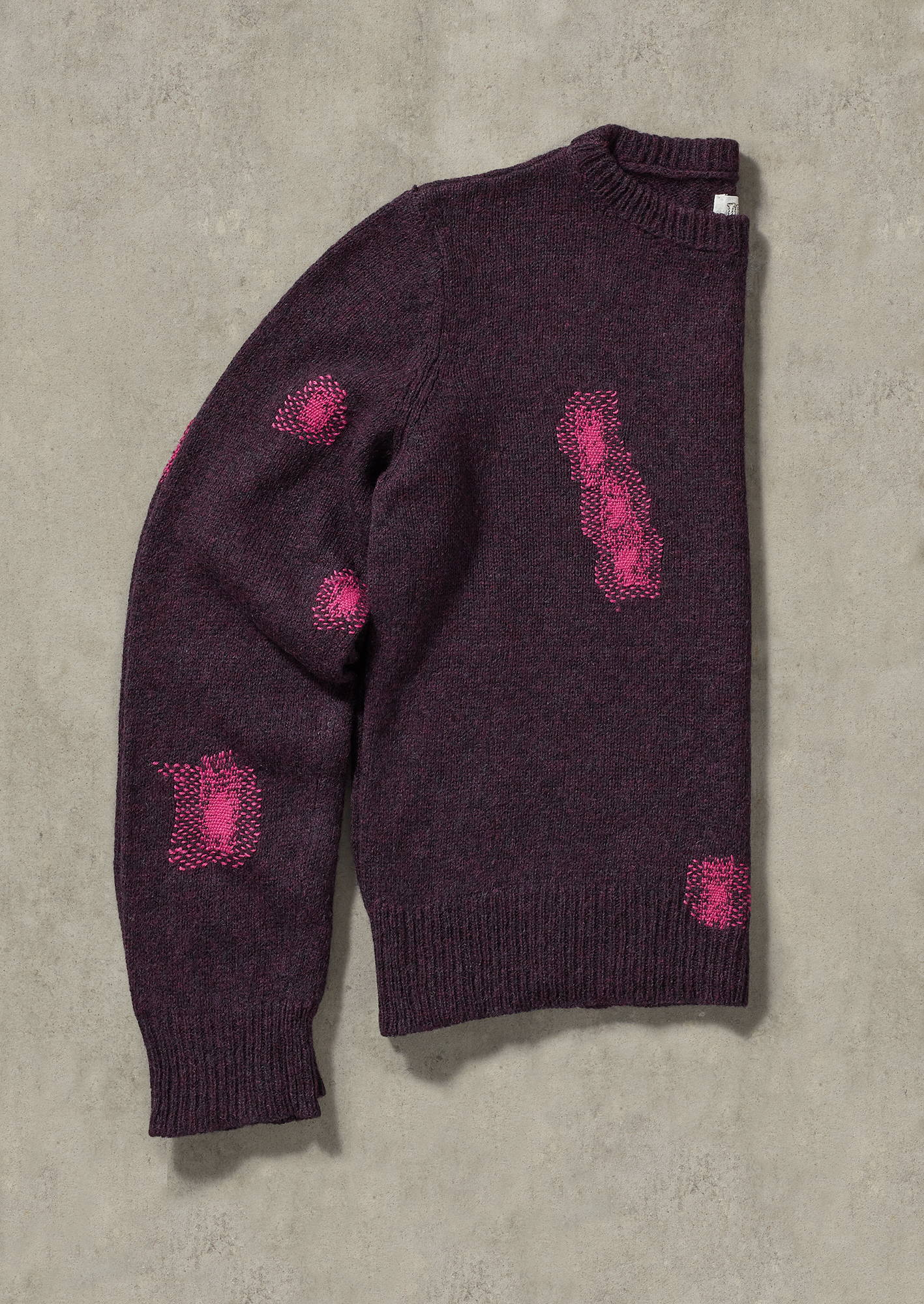 Purple sweater from TOAST with mended holes.