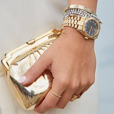 Hand with Rolex watch and bracelets