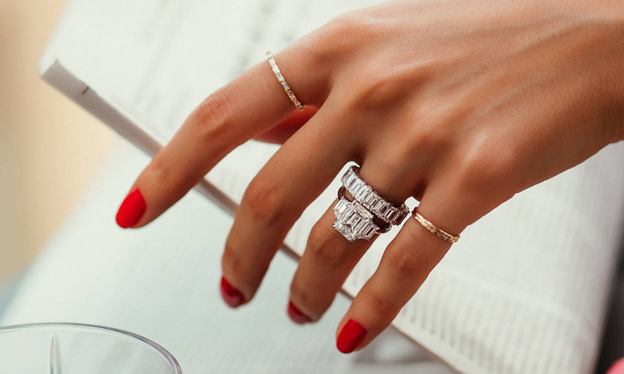 Close-up of model wearing Ring Concierge bespoke engagement ring and eternity band