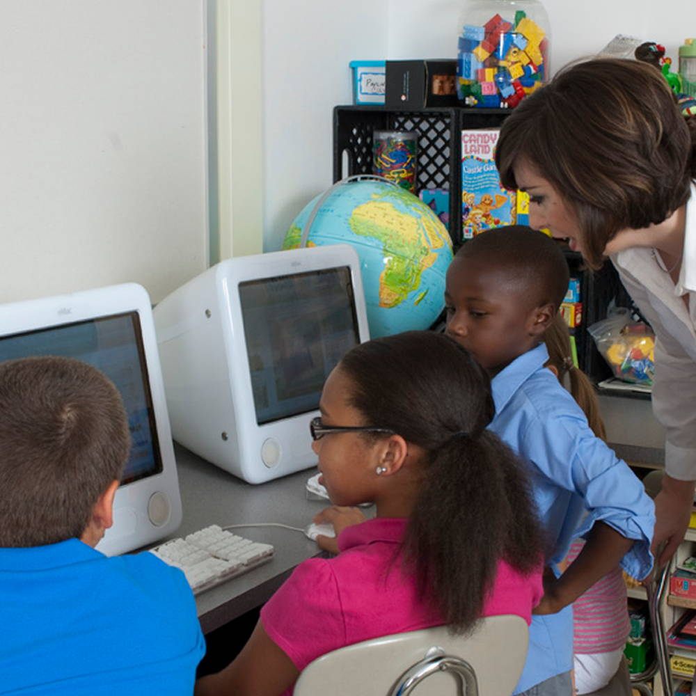 students with teacher in classroom using computers