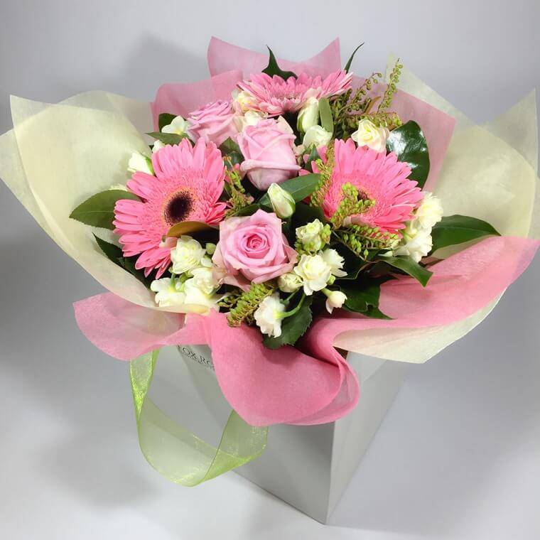 Flower gift bag filled with soft coloured roses and other flowers