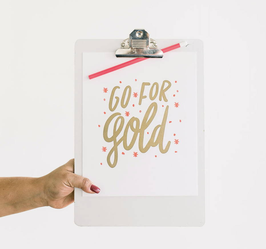 Girl holding a clip board with an inspiring art print with lettering 'Go for Gold.'
