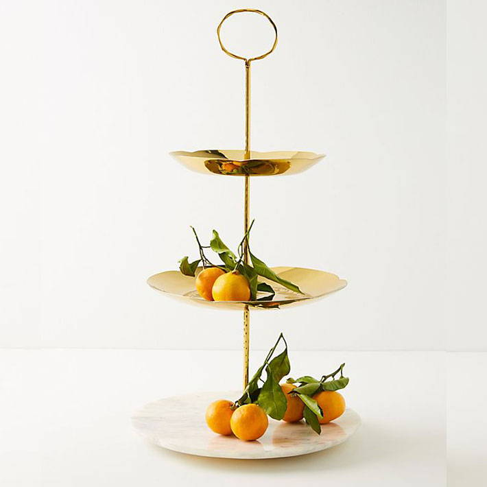 A three tiered serving platter with white and gold plates and oranges on top.