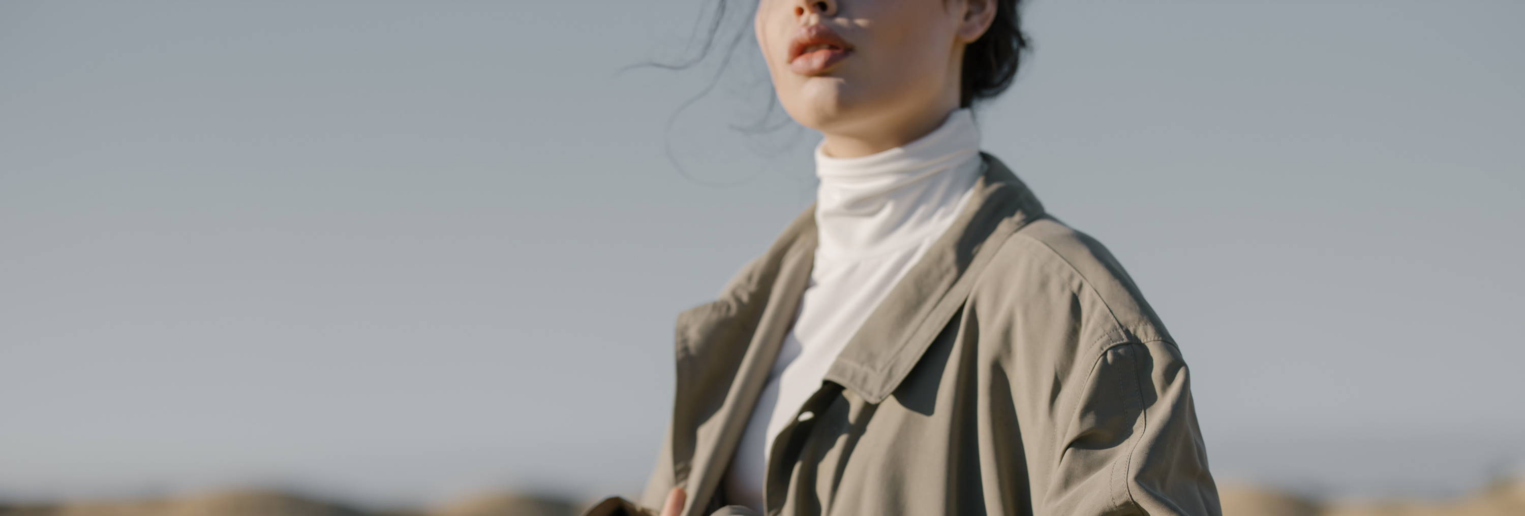 woman wearing white turtleneck and beige trench coat