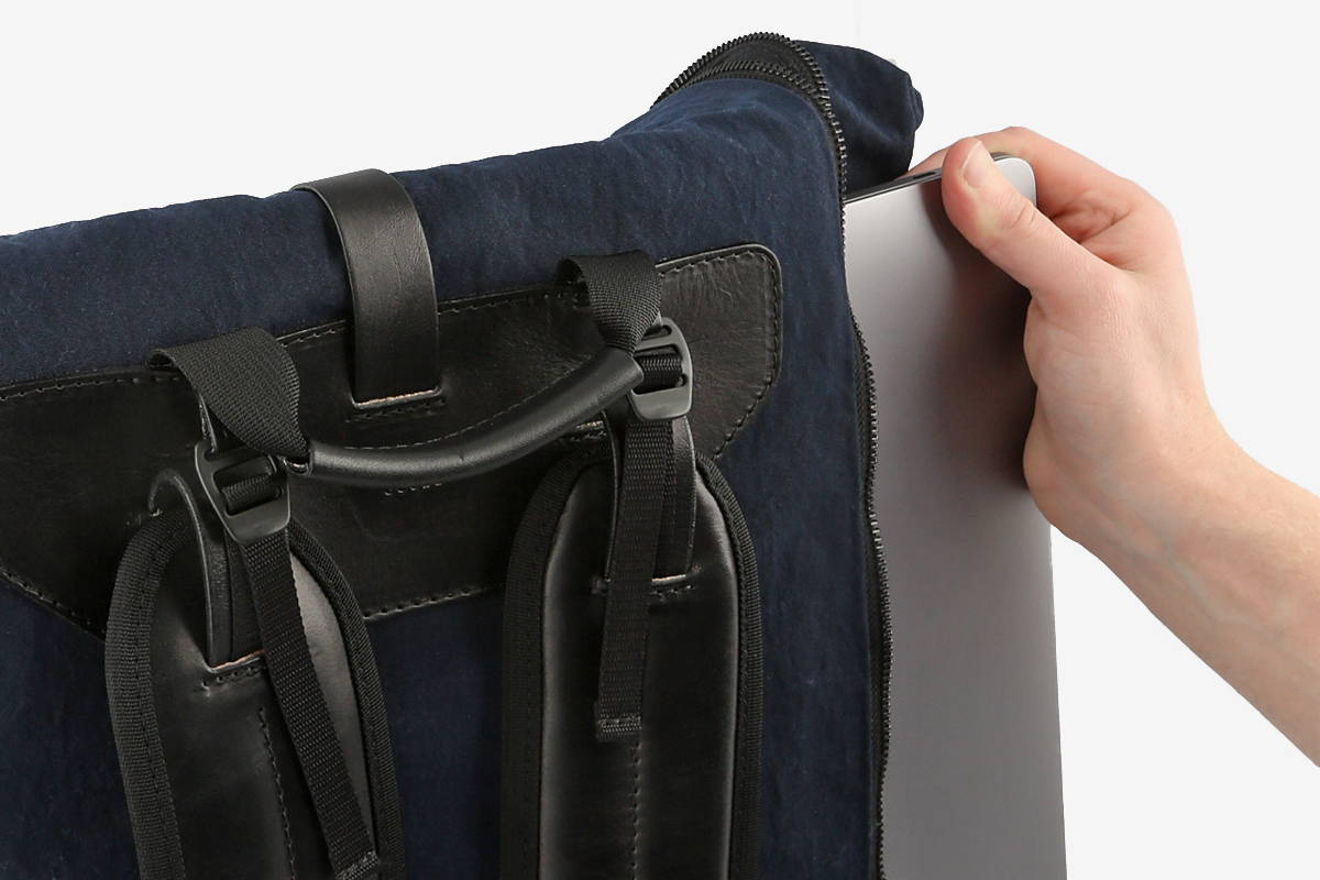 Pulling a Macbook out of the side of a navy blue backpack.