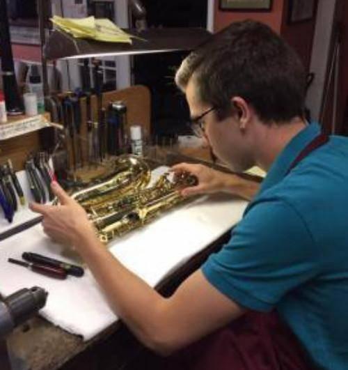 Brennan Lagan repairing a saxophone