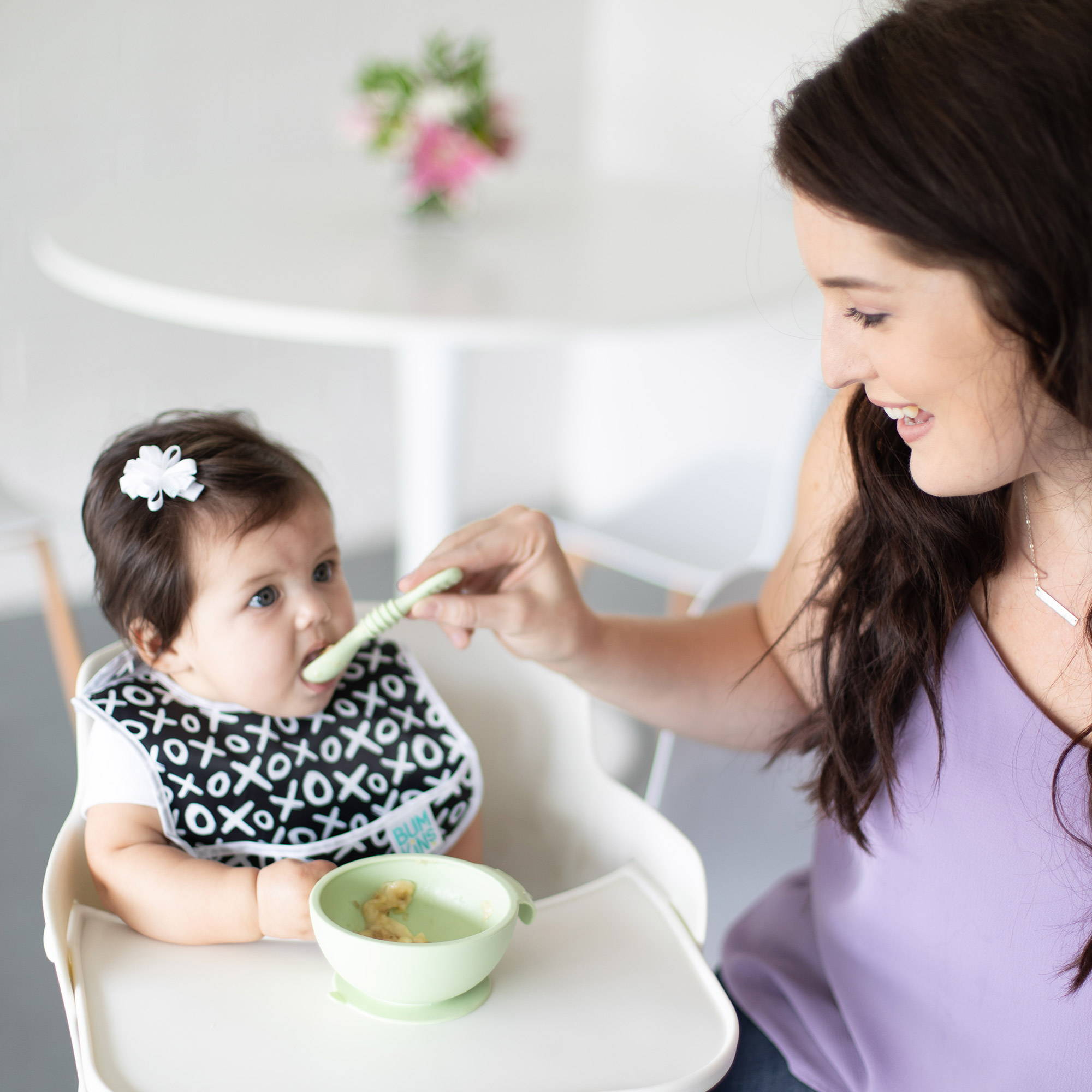 mom feeding her baby from a bumkins first feeding set with a bumkins silicone dipping spoon