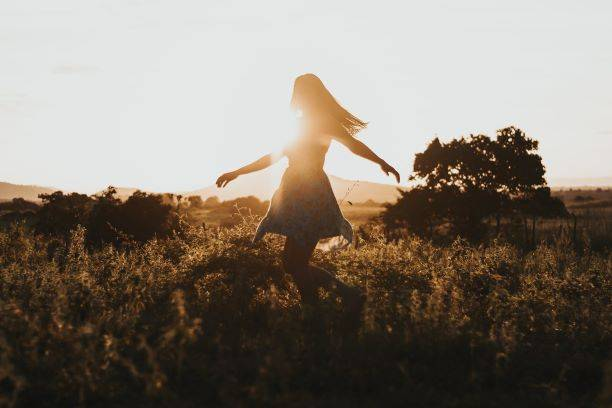 Woman Turning Around On Green Fields With Sun Shining