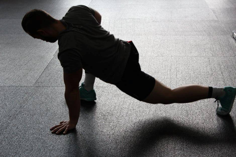 A man in training gear stretches before his workout.