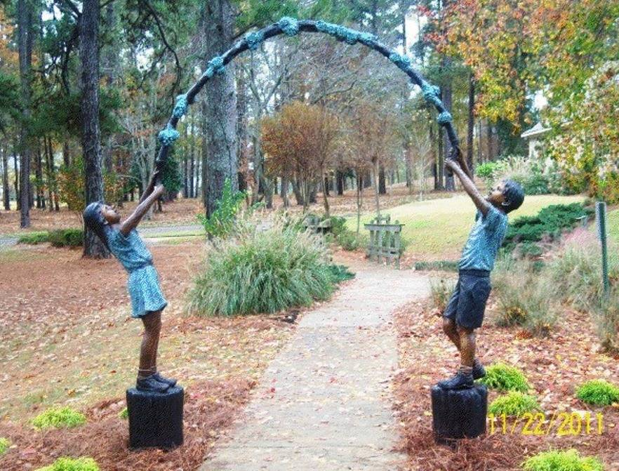 Bronze statue of a boy and girl holding an arbor in the park