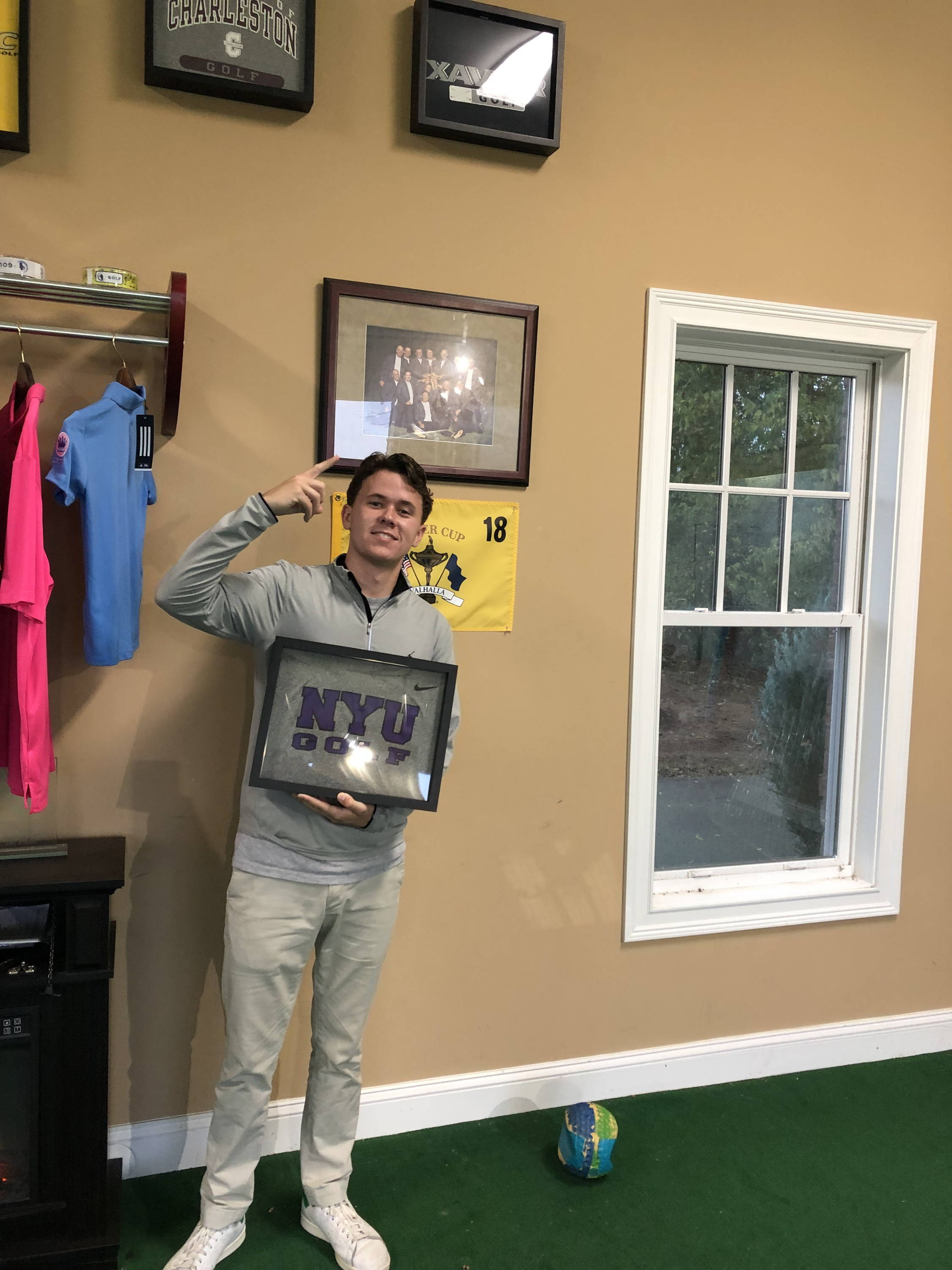 Golfer and Shart.com Customer holding a Shart Original T-Shirt Frame with an NYU Golf team tee shirt
