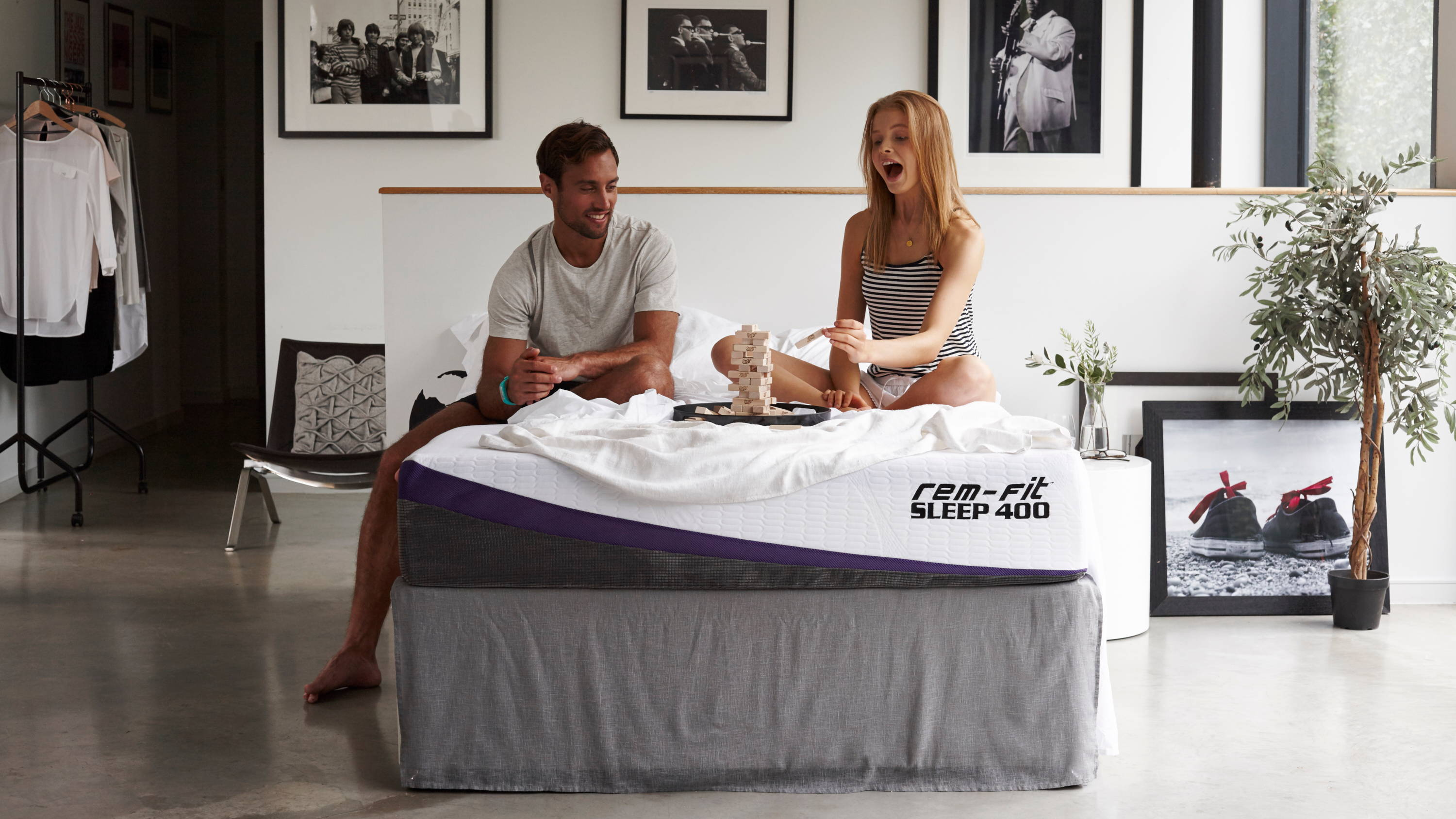 REM-Fit header image. couple playing jenga on rem-fit 400 mattress