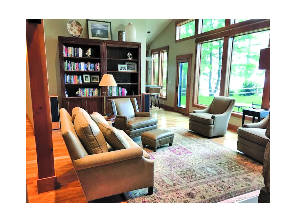 living room scene with tan couch and three arm chairs. two bookcases in background