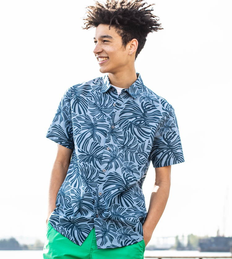 Man wearing patterned button up and cargo shorts