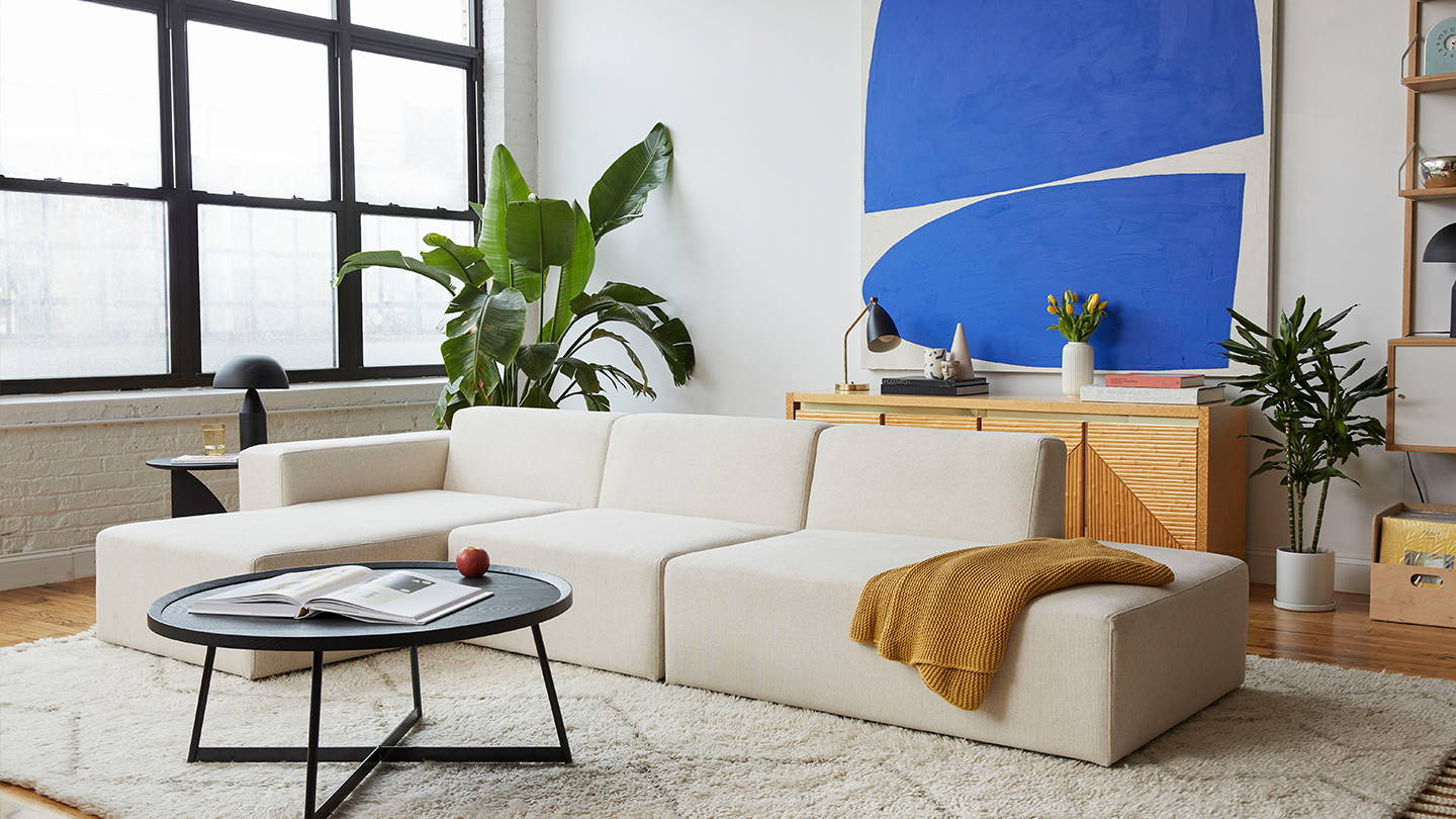 A white sectional in a bright room with bold blue art.