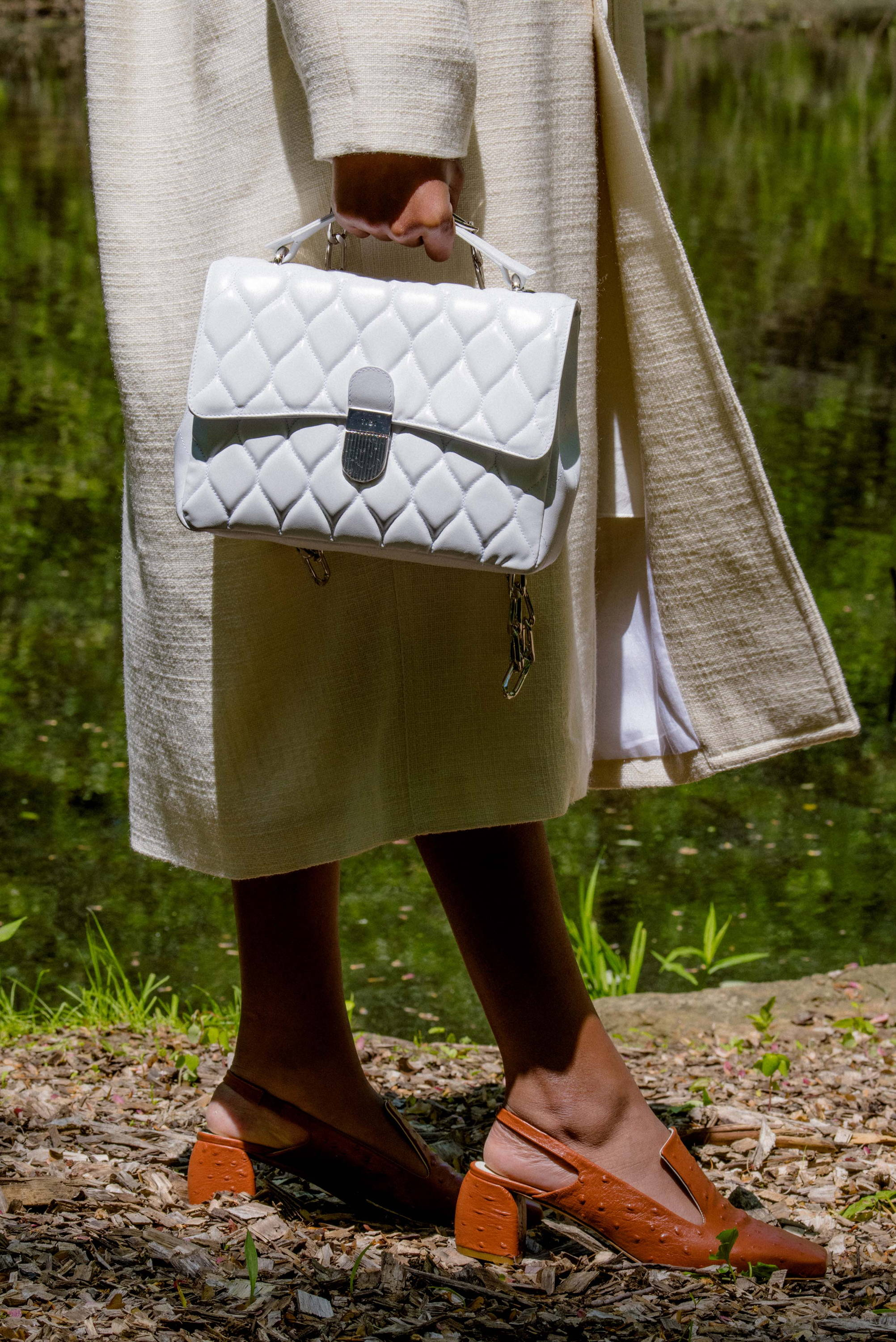 lower half of model holding white quilted bag and the brown ostrich evon heel.