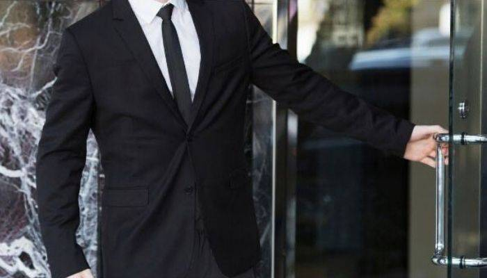 Man wearing black suit and tie opening door