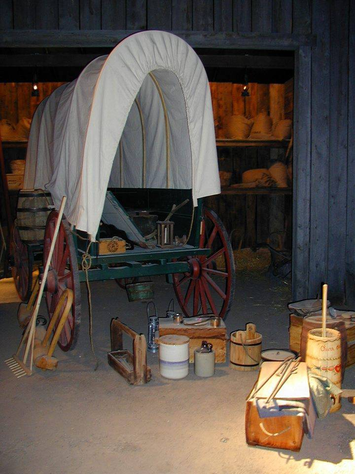 A covered wagon with supplies for the trek west  on display in the interpretive area within the Trail Center.