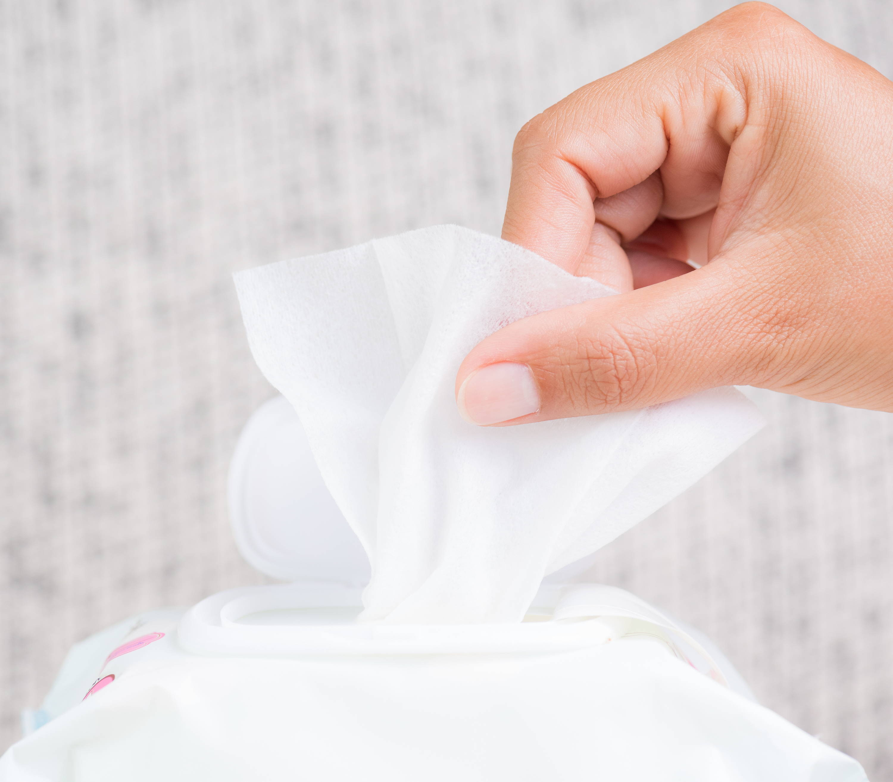 Hand grabbing a disposable wipes