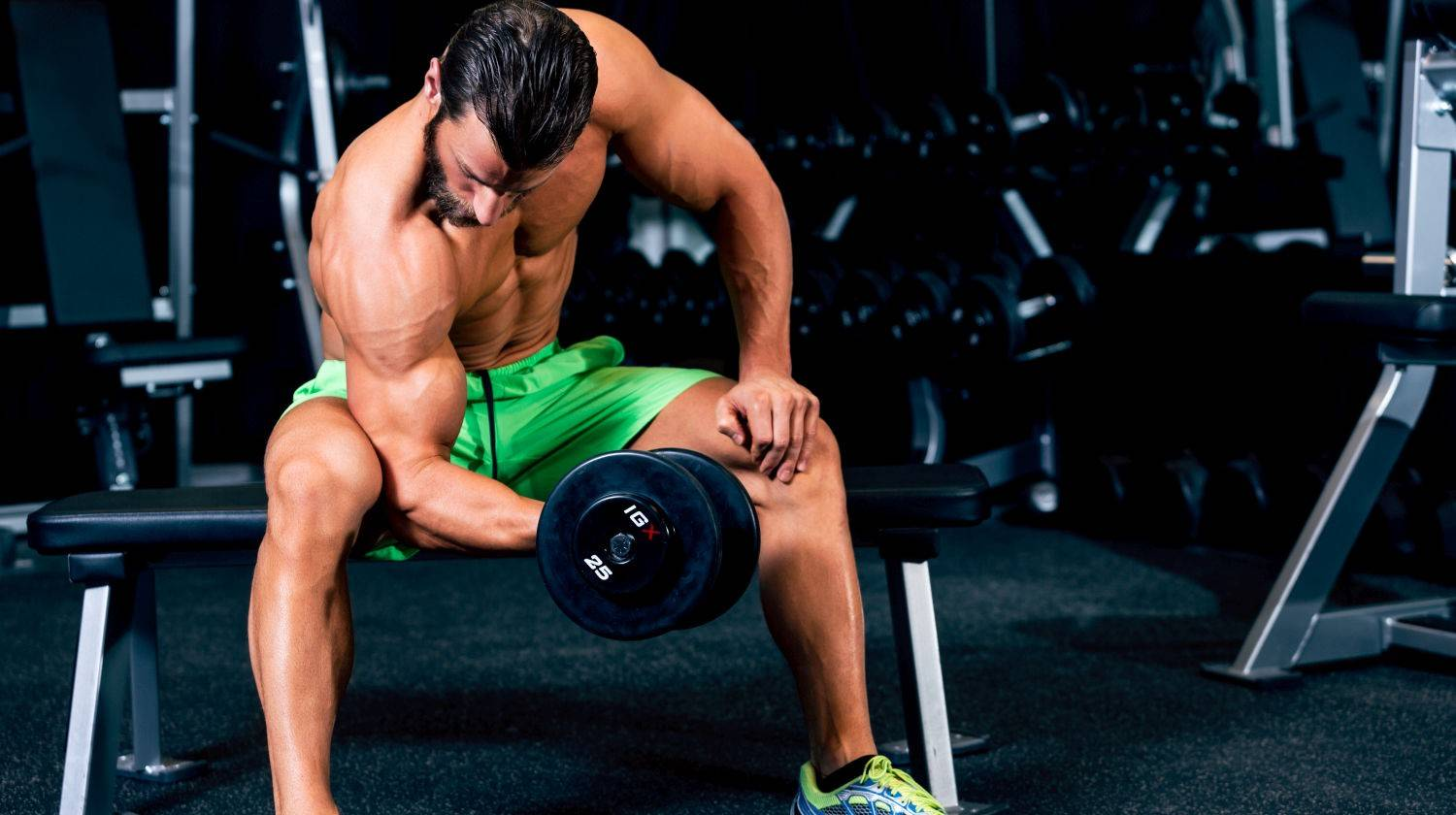 Ambassador Tim McComsey doing bicep curls in the gym   Muscle Building Diet: Best Foods to Eat For Muscles and Fast Recovery   Featured   best foods for gaining muscle