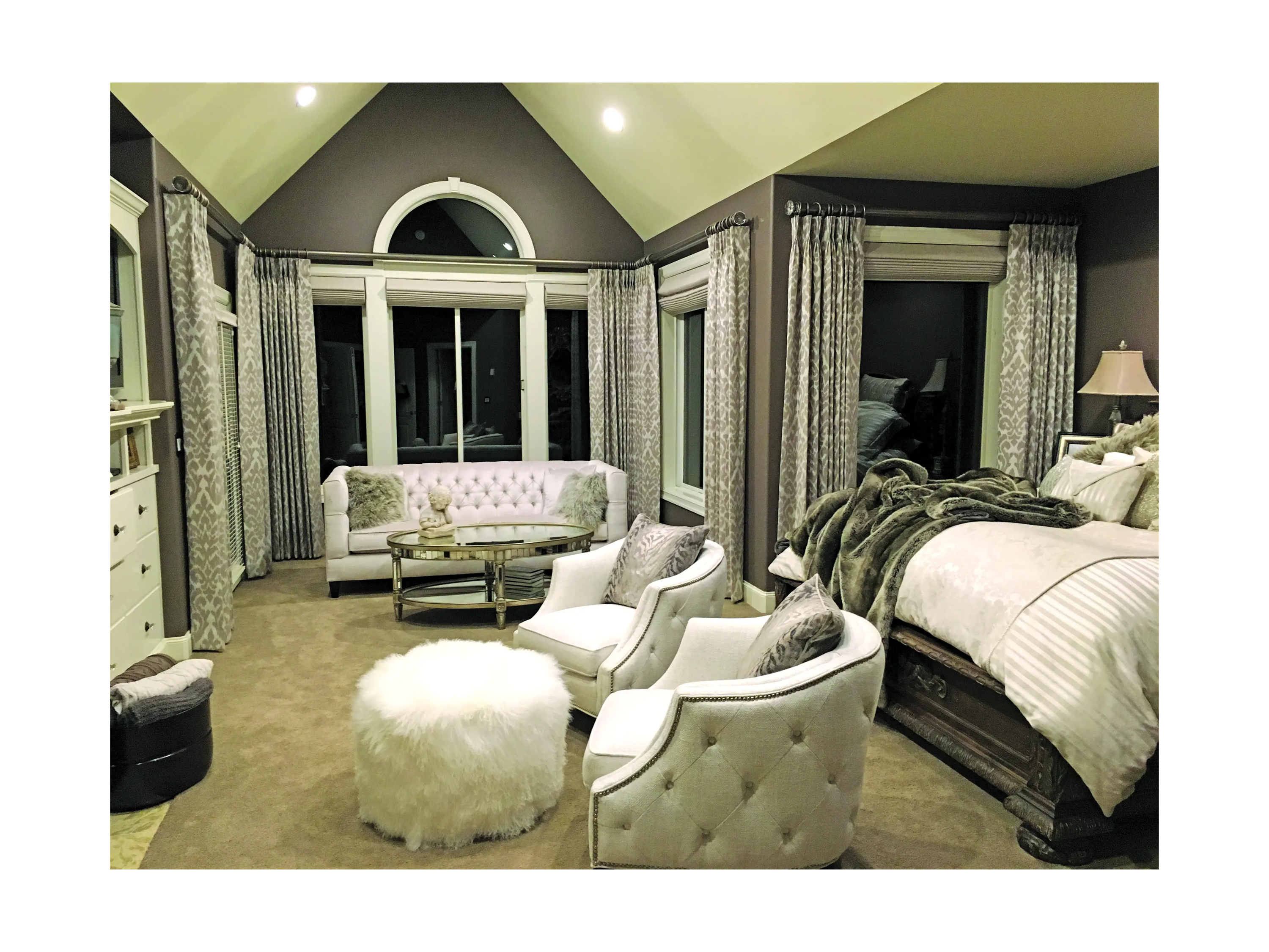 bedroom scene with two white arm chairs and furry ottoman at foot of bed. White tufted sofa in background