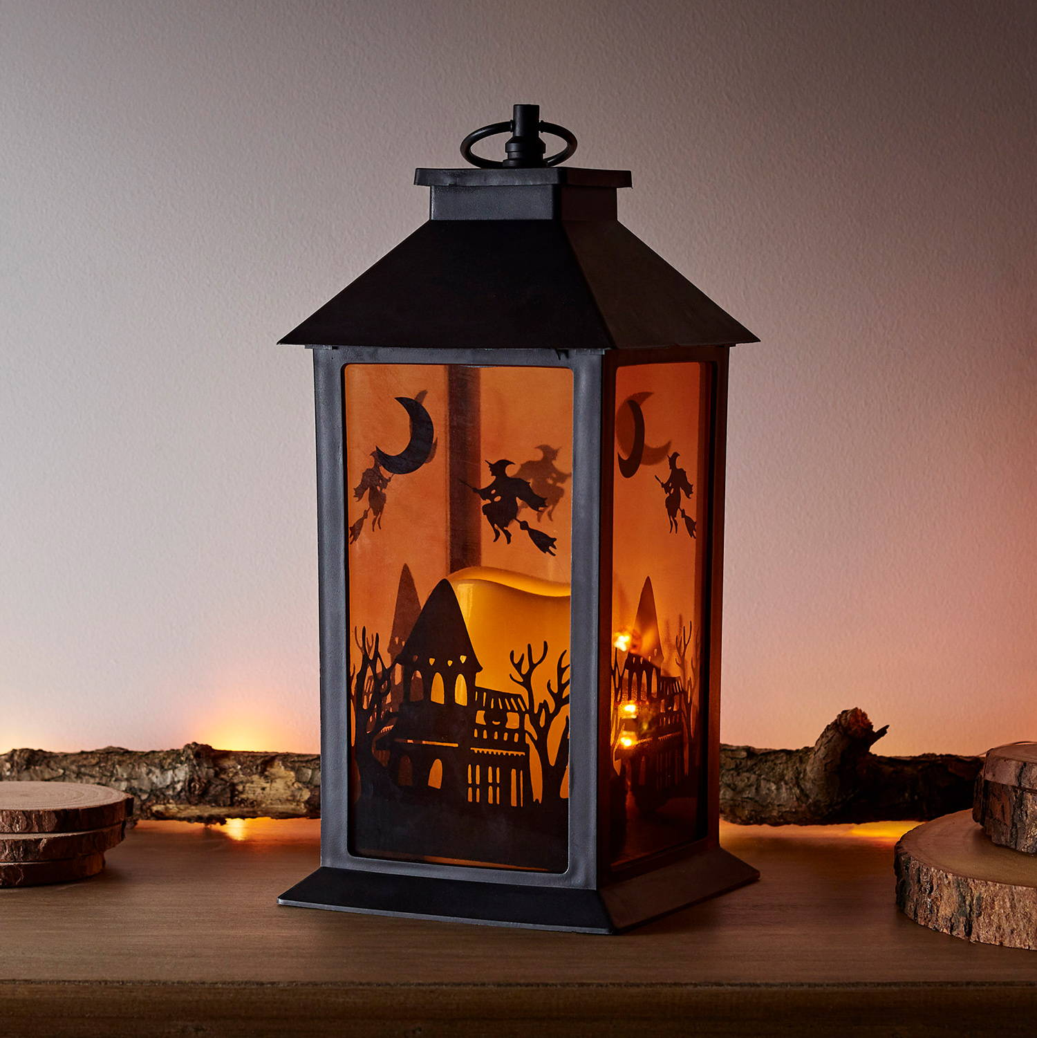 Outdoor halloween lantern featuring an LED candles encased with a haunted house scene on the glass