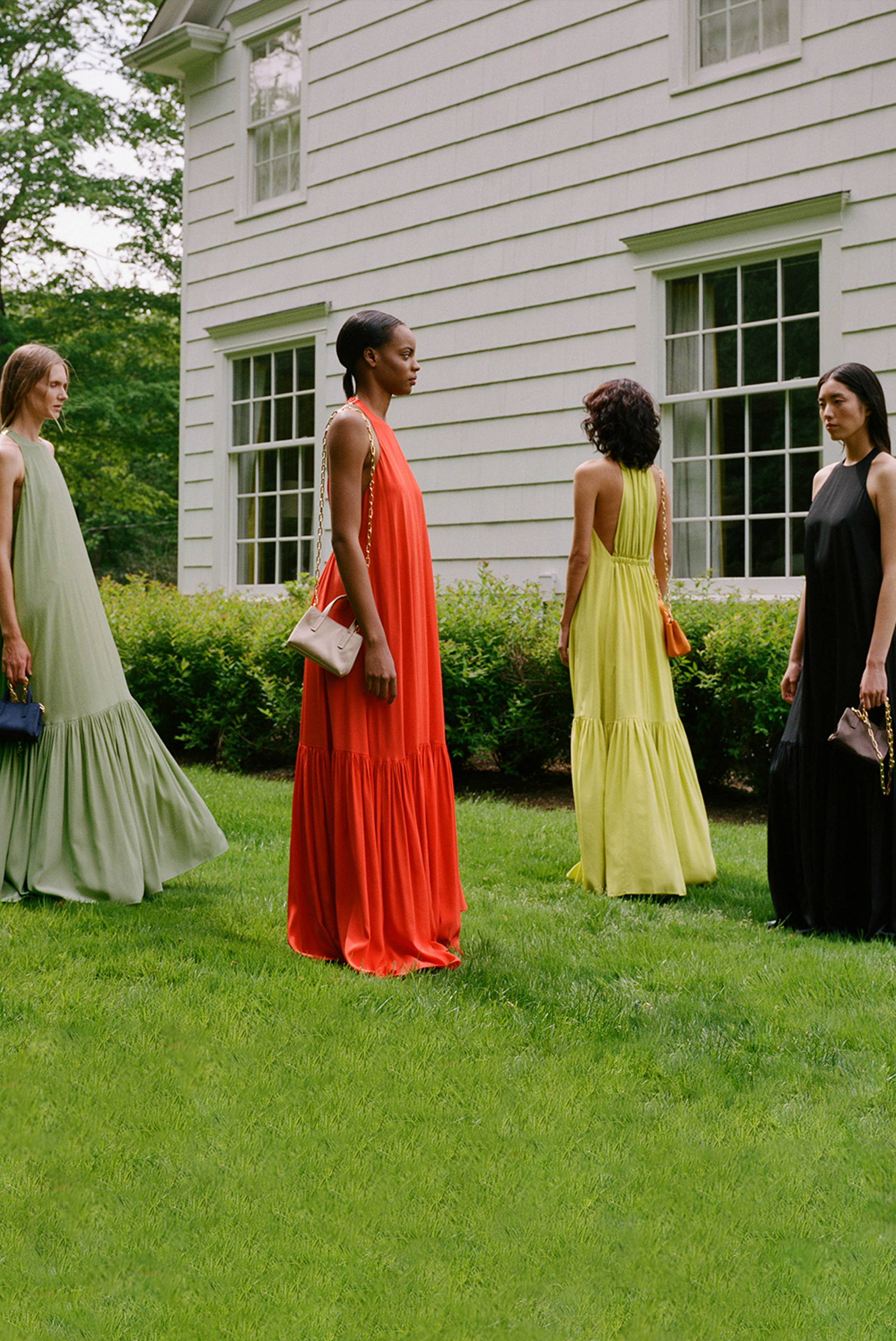 Four models standing in front of a white house all wearing the Heavy Silk CDC Halter dress from Resort 2020.